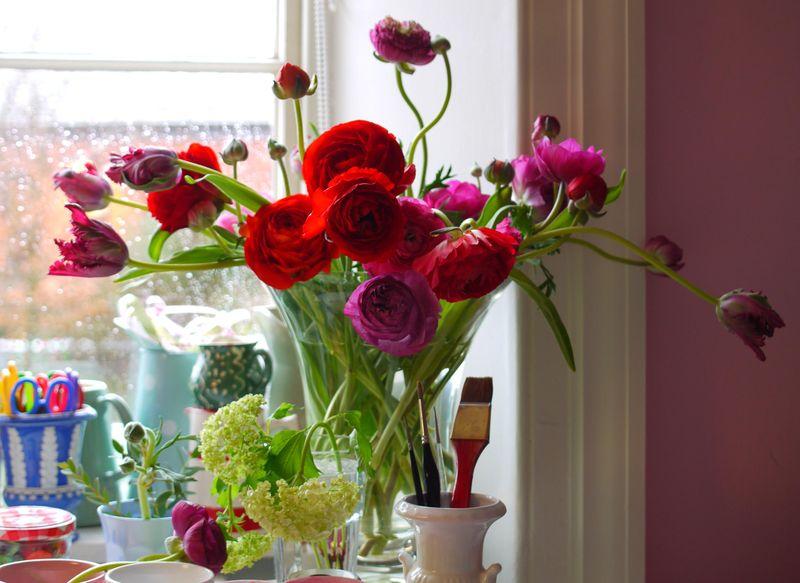 Flowers-on-desk,-rain-on-wi